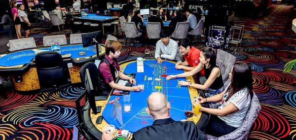 Players at a Baccarat Table inside the Queenco Casino